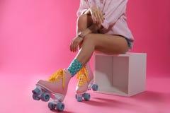 Jovem mulher com os patins de rolo retros no fundo da cor, close up imagem de stock