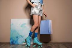 Jovem mulher com os patins e os sacos de compras de rolo retros contra a parede da cor fotos de stock