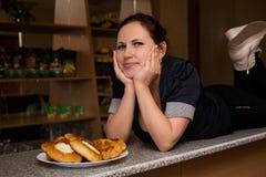 Jovem mulher com os peitos bonitos na barra com tortas foto de stock royalty free