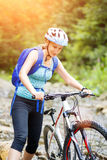 Jovem mulher com passeio da bicicleta a angra da montanha Fotografia de Stock