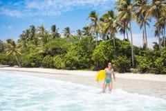 Jovem mulher com placa de ressaca na praia tropical imagem de stock royalty free