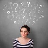 Jovem mulher com pontos de interrogação acima de sua cabeça Fotografia de Stock Royalty Free