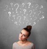 Jovem mulher com pontos de interrogação acima de sua cabeça Foto de Stock