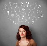 Jovem mulher com pontos de interrogação acima de sua cabeça Fotos de Stock