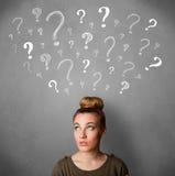 Jovem mulher com pontos de interrogação acima de sua cabeça Imagens de Stock Royalty Free