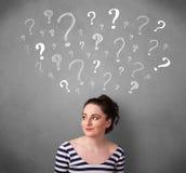 Jovem mulher com pontos de interrogação acima de sua cabeça Imagem de Stock Royalty Free