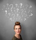 Jovem mulher com pontos de interrogação acima de sua cabeça Imagem de Stock
