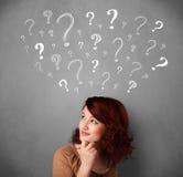 Jovem mulher com pontos de interrogação acima de sua cabeça Imagens de Stock