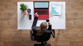Jovem mulher com rabo de cavalo que datilografa no portátil e no café bebendo, sentando-se atrás da tabela com originais, topshot filme