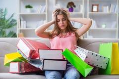 A jovem mulher com sacos de compras dentro dirige no sofá foto de stock