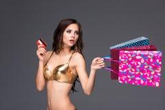 Jovem mulher com sacos de compras e cartão de crédito sobre Imagens de Stock Royalty Free