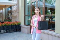 Jovem mulher com sacos de compras que anda na rua da cidade fotografia de stock