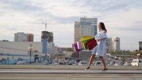 A jovem mulher com sacos exulta ap?s a compra uma mulher com sacos coloridos vai perto da loja Venda nas lojas cheerful vídeos de arquivo