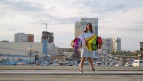 A jovem mulher com sacos exulta ap?s a compra uma mulher com sacos coloridos vai perto da loja Venda nas lojas cheerful filme