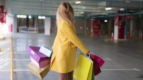 A jovem mulher com sacos exulta ap?s a compra Uma mulher loura com os sacos multi-coloridos ao lado da loja Venda nas lojas vídeos de arquivo