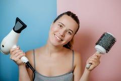 Jovem mulher com secador e pente de cabelo Tiro do estúdio fotos de stock