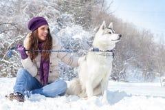 Jovem mulher com seu cão na neve Fotos de Stock
