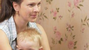 Jovem mulher com seu filho que senta-se em casa no sofá com controlo a distância da tevê Olhe a tela atentamente video estoque