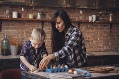 Jovem mulher com seus ovos da páscoa pequenos da pintura do filho na cozinha fotografia de stock