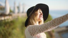 A jovem mulher com smartphone faz o selfie no café perto do mar filme