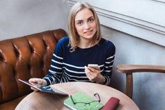 Jovem mulher com sorriso do smartphone e da tabuleta Uma moça de sorriso com tabuleta e um telefone, e a aprendizagem do descanso Foto de Stock