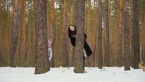A jovem mulher com sua filha espreita fora da árvore na floresta do inverno filme