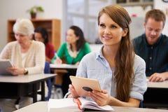 Jovem mulher com tablet pc em uma classe do ensino para adultos fotografia de stock