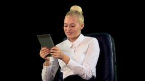 Jovem mulher com a tabuleta na cadeira Laughting Alpha Channel médio filme