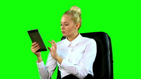 Jovem mulher com a tabuleta na cadeira Tela verde médio filme