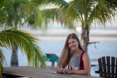 Jovem mulher com a tabuleta na praia foto de stock