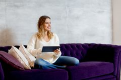 Jovem mulher com a tabuleta no sofá imagens de stock