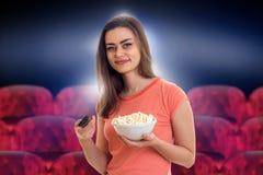 Jovem mulher com telecontrole e pipoca da tevê imagem de stock