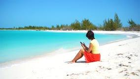 Jovem mulher com telefone celular durante férias tropicais da praia Turista que usa o smartphone móvel vídeos de arquivo