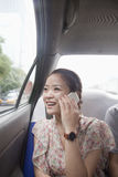 Jovem mulher com telefone celular no táxi Imagens de Stock