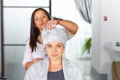 Jovem mulher com a toalha na cabeça no cabeleireiro Imagem de Stock