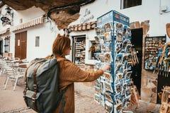 A jovem mulher com trouxa está olhando um suporte do cartão em uma vila pequena de spain foto de stock
