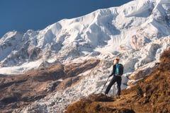 Jovem mulher com a trouxa no pico de montanha Imagens de Stock