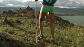 Jovem mulher com trouxa que anda em volta das montanhas e do lago video estoque