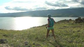 Jovem mulher com trouxa que anda em volta das montanhas e do lago filme