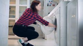 A jovem mulher com um braço biônico está tomando a roupa da máquina de lavar