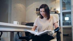 A jovem mulher com um braço cybernetic está lendo um livro video estoque