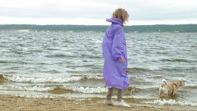 Jovem mulher com um c?o na praia pelo rio video estoque