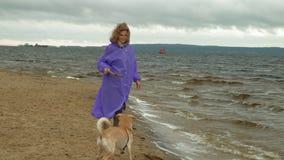 Jovem mulher com um c?o na praia pelo rio filme