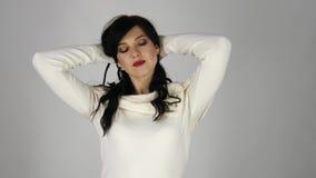 Jovem mulher com um cabelo preto que tem o divertimento que sorri e que toca em seu cabelo no estúdio video estoque