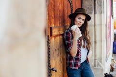 Jovem mulher com um chapéu ao lado de uma porta de madeira velha Fotografia de Stock Royalty Free
