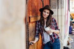 Jovem mulher com um chapéu ao lado de uma porta de madeira velha Foto de Stock Royalty Free