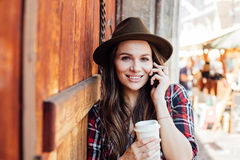Jovem mulher com um chapéu ao lado de uma porta de madeira velha que fala no cel Foto de Stock