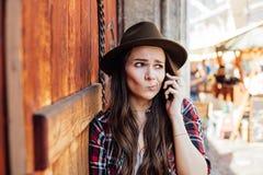 Jovem mulher com um chapéu ao lado de uma porta de madeira velha que fala no cel Imagem de Stock Royalty Free