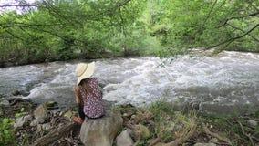 Jovem mulher com um chapéu que senta-se por um rio france filme
