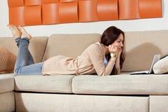 Jovem mulher com um computador no sofá Imagens de Stock Royalty Free